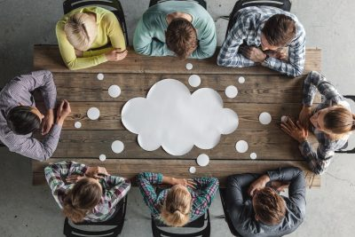Business teamwork brainstorming planning meeting concept, people sitting around the table with white paper shaped like dialog cloud