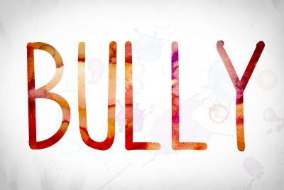 "The word ""Bully"" written in watercolor washes over a white paper background concept and theme."