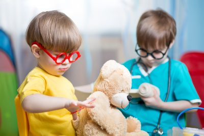 Kids playing doctor and curing plush toy at home