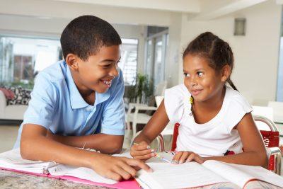 Two Children Doing Homework Together In Kitchen