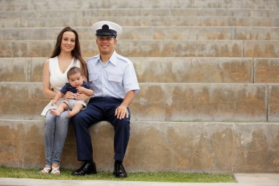 Military family smiles and poses at the park