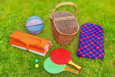 Picnic scene. Basket, blanket, racquetball and ball in the grass. Tilt-shift effect in background.