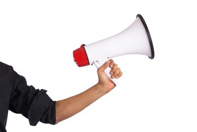 Hand holding megaphone on white background