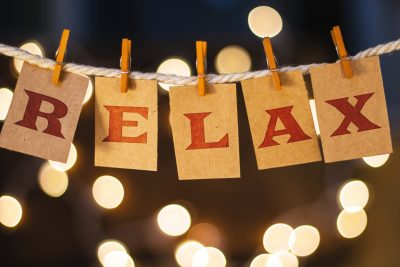 The word RELAX printed on clothespin clipped cards in front of defocused glowing lights.