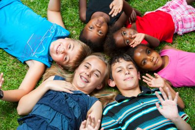 Diverse multiracial group of kids laying together joining heads together in a circle