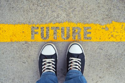 Person with sneakers on the asphalt road with yellow line with the words Future for the title symbolizing - Step into the future.