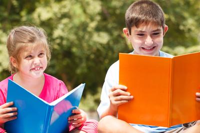 Happy children of three sitting on grass with books