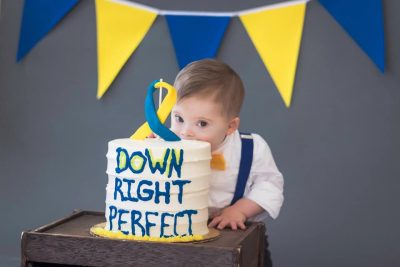 Child with down syndrome munches down on a cake titled down right perfect