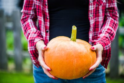 Young casual woman holding pumpkin in garden.