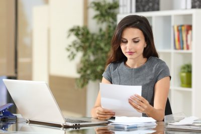 A woman is at her desk office setting looking over a document or letter
