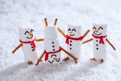 Happy funny marshmallow snowmen are having fun in snow