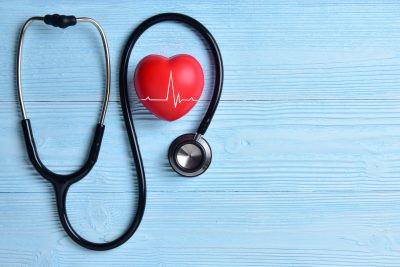 Red heart with stethoscope on blue wooden background - representing healthcare