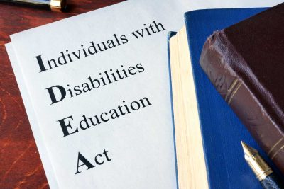 Books on top to a document with the Words IDEA which stands for Individuals with Disabilities Education Act