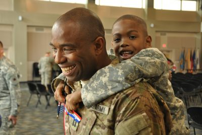 Male service member carrying a young boy piggyback, both smiling