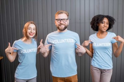 Three young adults proudly pose pointing at their shirts that say volunteer on them