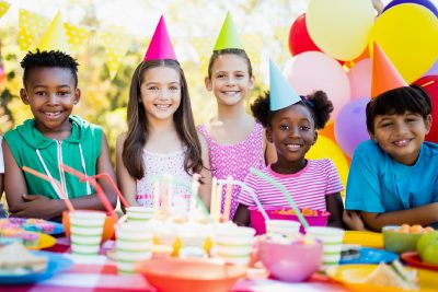 A group of Diverse children smile at a birthday party