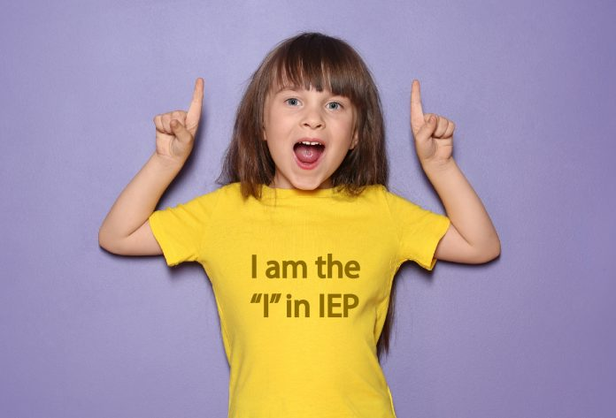 Little girl smiles and poses with the shirt that says I am the I in IEP