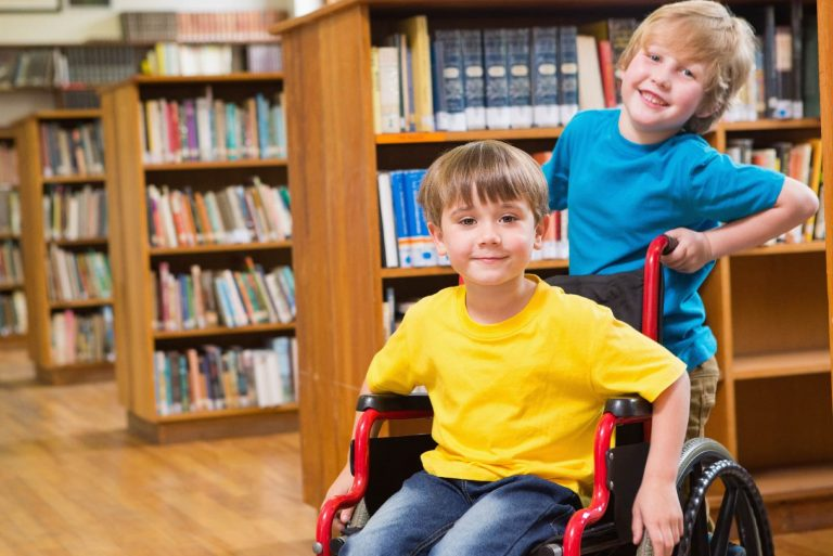 Two smiling boys at the library one is a wheelchairn