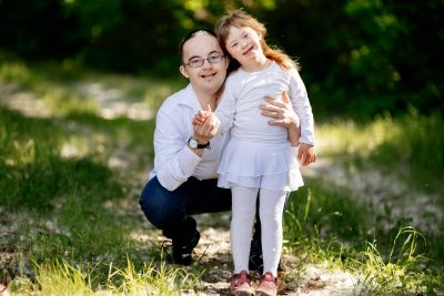 Dad with Down Syndrome poses with his daughter both are smiling
