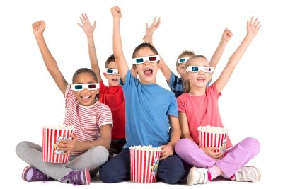 Kids sitting smiling with their hands up wearing 3D glasses and holding buckets of popcorn