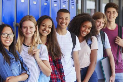 A group of diverse teens pose and smile in front of blue lockers