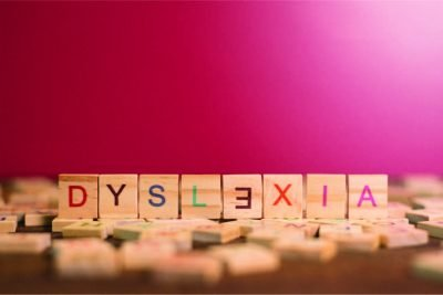 A pink background with word tiles spelling the word Dyslexia