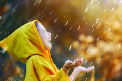 Child wearing a raincoat smiles under the rain