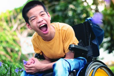 A boy sitting on his wheelchair is smiling while being outside