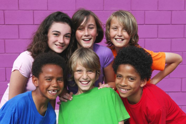 A happy group of diverse kids pose in front of a purple wall