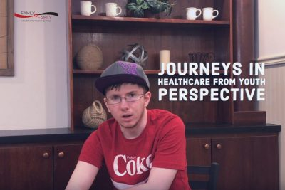 A young man poses with the sign Journeys in healthcare - a video about Tommy's diagnosis