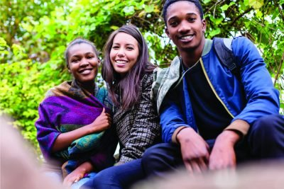 Three teen persons pose and smile at a park
