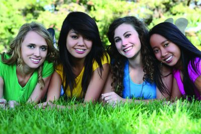 a group of diverse teen girls smile and pose at a park