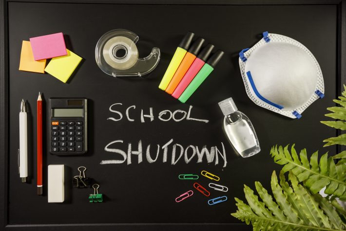 Caronavirus school shutdown concept with personal mask, hand sanitizer and stationery on black flat lay, school shutdown written with chalk on black board, overhead view