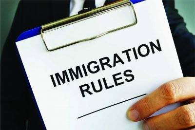 A clipboard is held up with a document names Immigration Rules