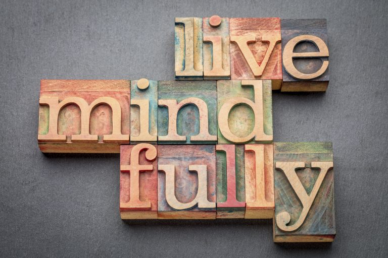 Paper stamp letters are put together to spell out the words live mindfully