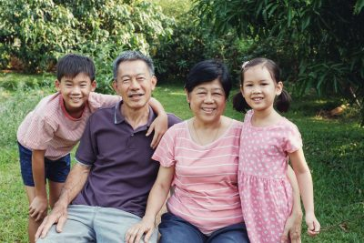 Asian grandchildren laughing with their grandparents in the park, Happy Asian family