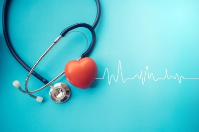 Healthcare concept, a stethoscope is displayed on a blue background with a red heart