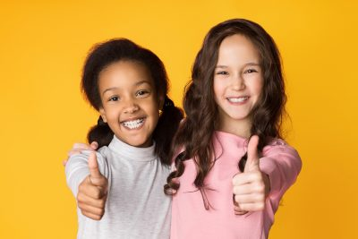 Two diverse girls smile and give a thumbs up