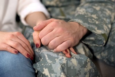 Male soldier holding girlfriends hand, farewell before military service, love