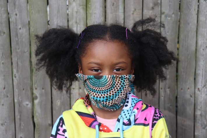 Cute African American Girl with pigtails wearing pattern fabric face mask outside with wooden fence background