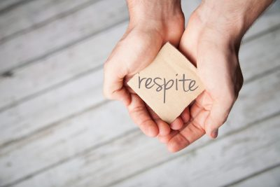 The word Respite is held from two kind hands
