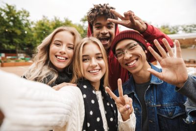 Group of cheerful multiethnic friends teenagers spending fun time together outdoors, taking a selfie