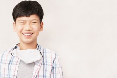 Stay safe and new normal concept, Young smart looking Asian teenage kid with medical face mask hanging on neck, smile to support stop spreading of coronavirus and Covid-19 pandemic campaign.