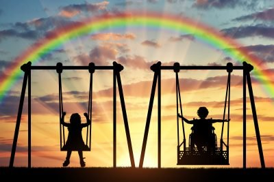Happy child is a person in a wheelchair riding an adaptive swing next to a typical child together. Concept of adaptive equipment for children with disabilities
